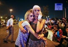 Fassungslose Passanten warten auf der Strasse vor dem Flughafen und umarmen sich. (Bild: Emrah Gurel)