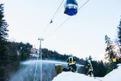 Während sich Retter zu den Gondeln abseilen, löscht die Feuerwehr den fiktiven Waldbrand. (Bild: Roger Grütter / Neue LZ)