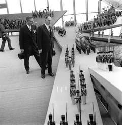 Bundesrat Paul Chaudet vom Militärdepartement (rechts) betrachtet während der Eröffnung am 30. April ein Schlachtszenario in einem Pavillion (Bild: Keystone / Str)