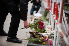 Ein Mann legt vor der französischen Botschaft in Berlin Blumen nieder. (Bild: EPA/Gregor Fisher)