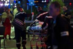 Dieser Nationalfeiertag ist ein trauriger. Rettungskräfte bringen eine verwundete Frau in den Ambulanzwagen. (Bild: OLIVIER ANRIGO)