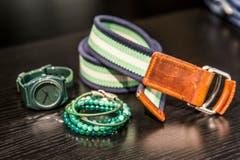 Eine Herren-Uhr in Jagdtgrün von Nixon, ein Gurt von Tommy Hilfiger und Perlen-Armbänder sind beim Männerwerk erhältlich. (Bild: Mareycke Frehner)