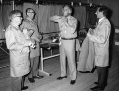 Joachim Fuchsberger war an den Olympischen Spielen von München im Jahr 1972 einer der Hauptsprecher. Hier probiert er, begutachtet von drei Schneidern, seine neue Uniform. (Bild: Keystone)