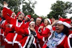 Lachende Weihnachtsfrauen im Vietnam: Sie gehören zu einer Lach-Yoga-Gruppe. (Bild: Keystone)