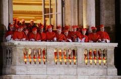 Die Kardinäle schauen zu, wie Papst Franziskus zu den Menschen auf dem Petersplatz spricht. (Bild: Keystone)