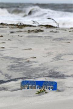 Durch «Sandy» ist so viel Sand angespült worden, dass nur noch ein kleiner Teil der Warntafel in Cape May aus den Dünen hervorlugt. (Bild: Keystone)