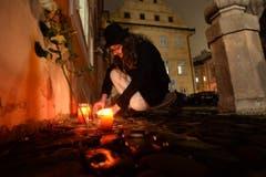 Ein Mann entzündet eine Kerze vor der französischen Botschaft in Prag. (Bild: Keystone)