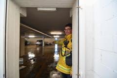 Feuerwehrkommandant Andreas Bösch steht im Türrahmen und zeigt auf die Türe. Das Wasser drückte sie ein und schleuderte sie durch die Tiefgarage. Das, obwohl die Türe sich gegen das Wasser geöffnet hätte. (Bild: Manuel Nagel)