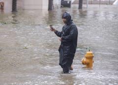 Ein Mann dokumentiert die Fluten in der Brickwell Avenue in Miami, Florida. (Bild: Keystone)