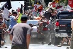 """Im August hatten sich mehrere Hundert Menschen aus verschiedenen ultrarechten Gruppen zu einer Kundgebung unter dem Motto """"Vereinigt die Rechte"""" in der amerikanischen Stadt Charlottesville versammelt. Sie protestierten gegen den Stadtratsbeschluss, wonach eine Statue des Konföderierten-Generals Robert F. Lee aus dem Amerikanischen Bürgerkrieg von 1861 entfernt werden sollte. Stunden vor der eigentlichen Veranstaltung kam es zu Prügeleien zwischen Rechten und Gegendemonstranten. Plötzlich eskalierte die Situation: Ein Mann raste mit seinem Auto absichtlich in eine Gruppe Demonstranten und tötete eine Frau. 19 Menschen wurden verletzt. (Bild: RYAN M. KELLY (AP The Daily Progress))"""