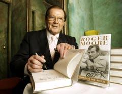 """Roger Moore unterschreibt sein Buch """"The World is My Bond"""" während einer Pressekonferenz 2008. (Bild: Keystone)"""