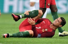 Nach einem Tackle hält sich der Portugiesische Fussballspieler Christiano Ronaldo das Bein. (Bild: Keystone)