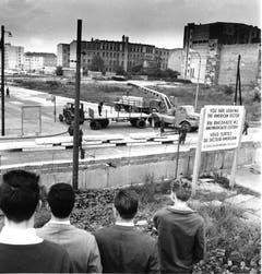 Westberliner schauen am 12. September 1961 an der Wilhelmstrasse in Berlin der Anlieferung vorgefertigter Betonbauteile zur Verstärkung der Berliner Mauer zu. (Bild: Keystone)