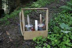 Klebeband, rote und weisse Farbe sowie eine Bürste gehören in das Holzgestell. Mit der Bürste entfernt Marthy das Moos auf den Steinen. (Bild: Jolanda Riedener)