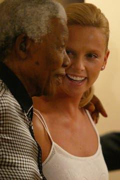 Friedensnobelpreistärger Nelson Mandela scherzt mit Oscargewinnerin und Landfrau Charlize Theron (2004). (Bild: Keystone)