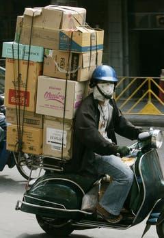 In Thailand fahren die Paketkuriere die Bestellungen ihrer Kunden ebenfalls auf der Vespa aus. (Bild: Keystone)