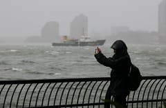Faszination Supersturm: Eine Frau fotografiert die Szene mit ihrem Handy. (Bild: Keystone)