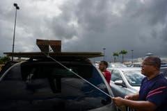 Zwei Männer binden Bretter auf ihrem Auto fest, um Fenster und Türen am Haus zuzunageln. (Bild: Keystone)