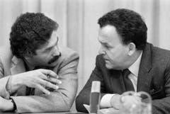 Oswald Sigg, der Informationschef des eidgenössischen Finanzdepartements, bespricht sich 1985 an einer Pressekonferenz mit Otto Stich. (Bild: Keystone)