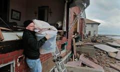 Peter Andrews bringt die Habseligkeiten aus dem zerstörten Haus seines Vaters. Andrews: «Wir haben schon viele Stürme erlebt und der einzige Schaden bisher entstand, als ein Mann der Nationalgarde einen Sandsack durch das Fenster warf.» (Bild: Keystone)