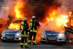 Feuerwehrleute löschen brennende Polizeiautos. (Bild: Keystone)