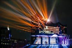 """Mit einer spektakulären Lichtshow auf und an der Fassade wurde die Elbphilharmonie im Januar in Hamburg eröffnet. """"Elphi"""", wie das Konzerthaus auch genannt wird, wurde mit dem Ziel gebaut, ein neues Wahrzeichen der Stadt darzustellen und ein """"Kulturdenkmal für alle"""" zu schaffen. Das 110 Meter hohe Gebäude am rechten Ufer der Norderelbe wurde nach über zehn Jahren Bauzeit fertig gestellt. (Bild: MARKUS SCHOLZ (DPA dpa))"""
