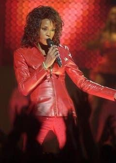Whitney Houston erfindet sich immer wieder neu, hier 2002 in einer roten Lederkluft und mit Rockermähne bei den MTV European Music Awards in Barcelona. (Bild: Keystone)