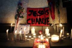 """Nach der Attacke auf die Redaktion des Satiremagazins """"Charlie Hebdo"""" haben Menschen in Gedenken an die Opfer ein Plakat mit der Aufschrift """"Je suis Charlie"""" sowie Kerzen aufgestellt in Paris. (Bild: Keystone)"""