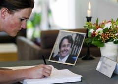 Eine Frau schreibt in ein Kondolenzbuch. (Bild: Keystone)