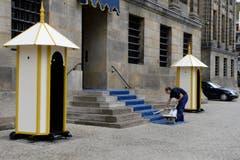 Der Teppich vor dem Königspalast wird gesaugt. (Bild: Keystone)