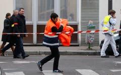 """Einsatzkräfte bei der Redaktion von """"Charlie Hebdo"""". (Bild: Keystone)"""
