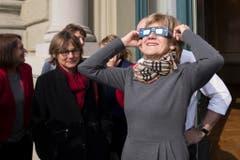 Die Basler SP-Nationalraetin Susanne Leutenegger Oberholzer verfolgt mit einer Schutzbrille das Naturspektakel der partiellen Sonnenfinsternis auf dem Balkon des Bundeshauses. (Bild: Keystone)