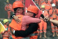 Alt-Bundesrat Adolf Ogi (links) und der damalige Verkehrsminister Moritz Leuenberger umarmen sich nach dem Hauptdurchschlag. (Bild: Keystone)