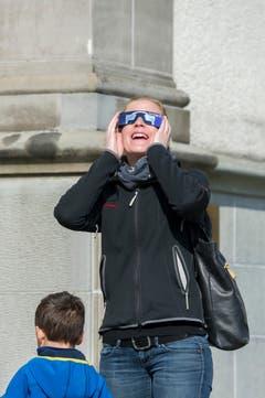 Man sieht wirklich etwas! Eine Frau ist entzückt von der Sonnenfinsternis. (Bild: Urs Bucher)