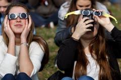 Nur mit Schutzbrille kann man überhaupt etwas sehen von der Sonnenfinsternis. (Bild: Keystone)