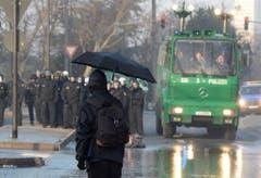 Ein maskierter Demonstrant mit einem Regenschirm steht Polizisten gegenüber. (Bild: Keystone)