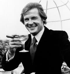 """Geschüttelt und nicht gerührt! Roger Moore mit Zigarre und Martini. Aufgenommen wurde dasd Bild 1972 während der Dreharbeiten zu """"Live and Let Die"""". (Bild: Keystone)"""