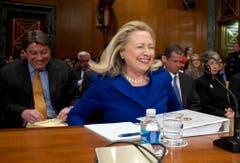 Hillary Clinton hat im Februar 2012 Probleme, sich richtig auf den Stuhl zu setzen und bricht deshalb in Gelächter aus. (Bild: Keystone)
