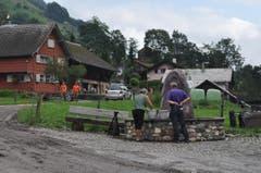 Der Melser Gemeindepräsident Guido Fischer spricht beim Dorfbrunnen mit einer betroffenen Anwohnerin. (Bild: Sarganserländer/Michael Kohler)