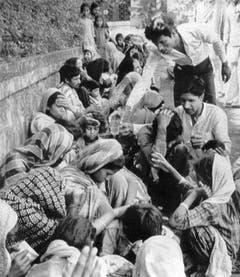 Den Opfern der Giftgaskatastrophe wird vor einem Spital Wasser verteilt, aufgenommen am 6. Dezember 1984. (Bild: Keystone)