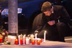 Ein Angestellter von Germanwings und Lufthansa zündet eine Kerze vor dem Hauptsitz von Germanwings an. (Bild: Keystone)
