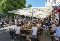 Menschen essen vor der roten Flora in Hamburg und geniessen die Ruhe und das Wetter während das Viertel von Anwohnern aufgeräumt wird. (Bild: Keystone)