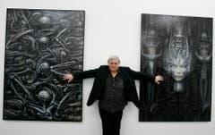 H.R. Giger posiert vor zwei seiner Bilder aus dem Jahre 1976 und 1974. (Bild: Keystone)