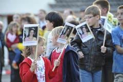 Schulkinder mit Fähnchen, auf denen die Miss abgebildet ist. (Bild: Hanspeter Schiess)