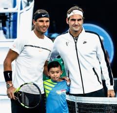 Der Spanier Rafael nadal und Roger Federer psoieren vor dem Spiel mit einem Ball-Buben. (Bild: Keystone)