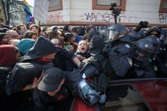 Polizisten versuchen die Protestanten in den Griff zu bekommen. (Bild: Keystone)