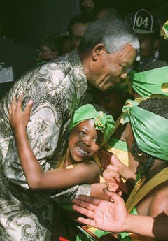 """Sie nennen ihn liebevoll """"Madiba"""": Nelson Mandela wird von einem Schulmädchen umarmt (1997). (Bild: Keystone)"""