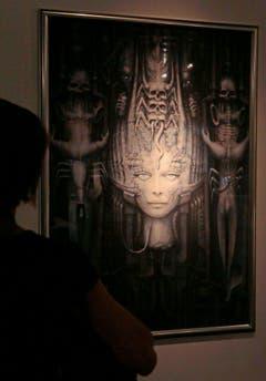 Ein Besucher betrachtet ein Giger-Bild an einer Ausstellung. (Bild: Keystone)