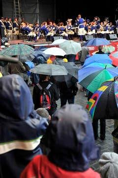 Fast mehr Regenschirme als Musiker: ein Bild, das sich bei Präsentationen in der Innenstadt am Samstag mehrfach zeigte. (Bild: Keystone)