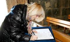 Eine Frau trägt sich in Seyne-les-Alpes in ein Kondolenzbuch für die Opfer ein. (Bild: Keystone)